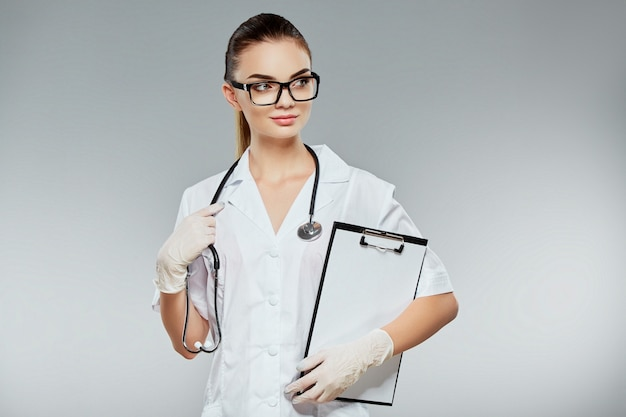 Прекрасный доктор с каштановыми волосами и обнаженным макияжем носит белую медицинскую форму, очки, стетоскопы и белые перчатки на сером фоне студии и держит заметки.