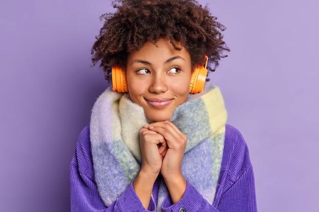 Милая мечтательная женщина с кудрявыми волосами держит руки вместе, смотрит в сторону и думает о чем-то приятном, слушает музыку через стерео электронные наушники, носит теплый шарф на шее. концепция хобби