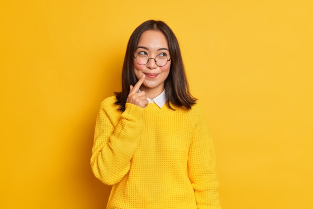 Lovely dreamy young asian woman with dark hair keeps finger near lips wears round transparent glasses and sweater.