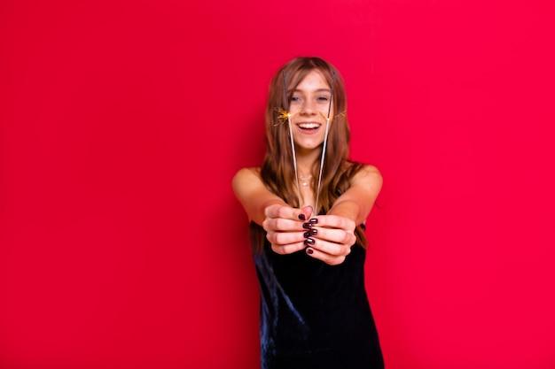 真っ赤な壁にポーズをとってパーティーを待っている輝きのあるイブニングブラックドレスの素敵なエレガントでスタイリッシュな女性