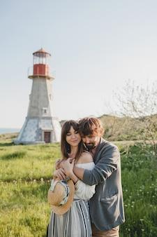 素敵な田舎を歩いて恋に幸せな若いスタイリッシュな流行に敏感なカップルを受け入れる