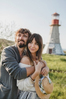 Lovely embracing happy young stylish hipster couple in love walking in countryside, summer style boho fashion
