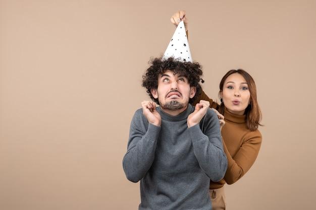 Le giovani coppie eccitate energiche adorabili indossano la ragazza sorridente del cappello del nuovo anno che sta dietro il ragazzo su gray