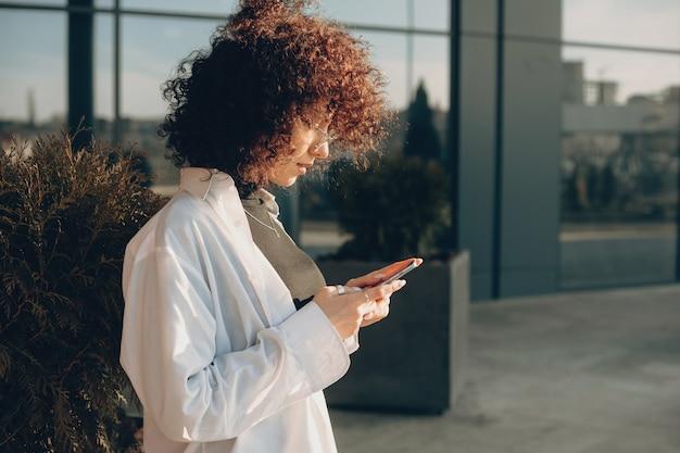 携帯電話でチャットしながら外でポーズをとる巻き毛の素敵な起業家