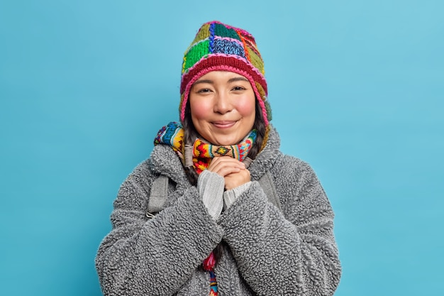 Bella femmina eschimese con le guance rosee tiene le mani unite e sorride piacevolmente vestita con un cappello caldo alla moda e un cappotto invernale vive nel luogo artico o al polo nord