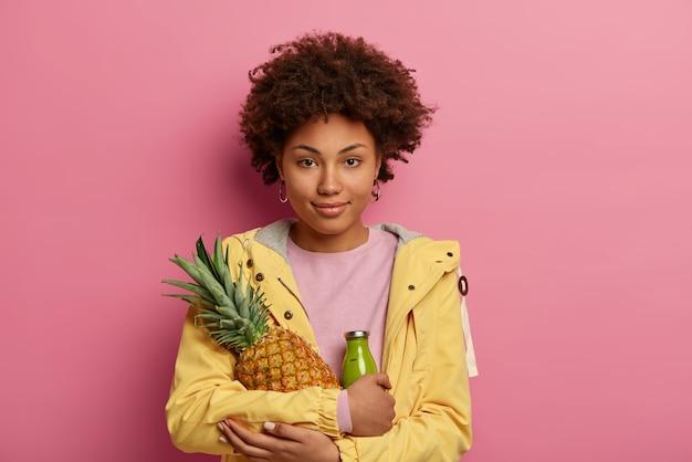 La bella ragazza etnica tiene il frullato di frutta verde appena miscelato in bottiglia e ananas, si mantiene a dieta e mangia sano, guarda direttamente la telecamera con un sorriso soddisfatto