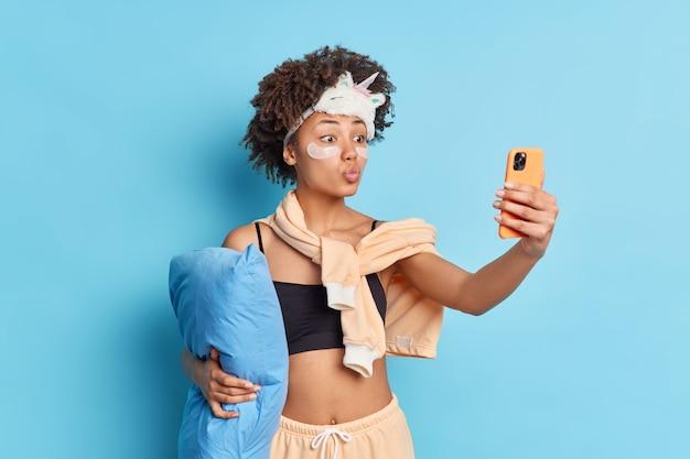 素敵なエスニック女性が自分の写真を作り、唇を丸く保ち、スマートフォンを正面に構え、青い背景の上に隔離された額にカジュアルな家庭用パジャマのスリープマスクを付けます。寝る前の自分撮り