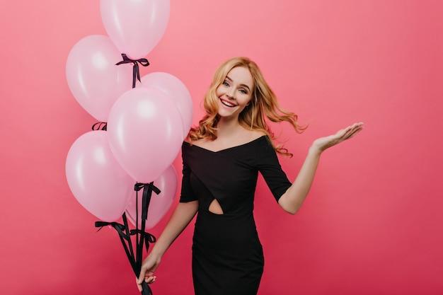 Bella ragazza europea che gode del servizio fotografico con palloncini rosa. incredibile modello femminile grazioso che balla nel suo compleanno.