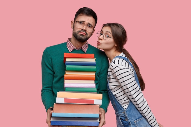 Lovely european schoolgirl going to kiss her boyfriend who holds large pile of books, stand closely to each other