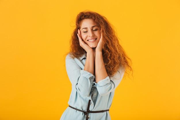 顔に手をつないで、目を閉じて笑って、黄色の背景で隔離の素敵なヨーロッパの女性