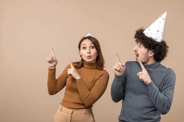 Le giovani coppie felici emozionanti adorabili portano il cappello del nuovo anno che indica sopra sull'immagine grigia