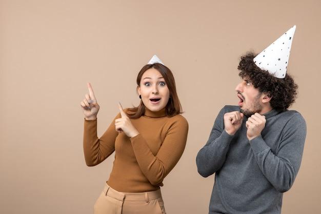 Le giovani coppie felici emozionanti adorabili portano il cappello del nuovo anno che indica sopra sull'immagine di riserva grigia