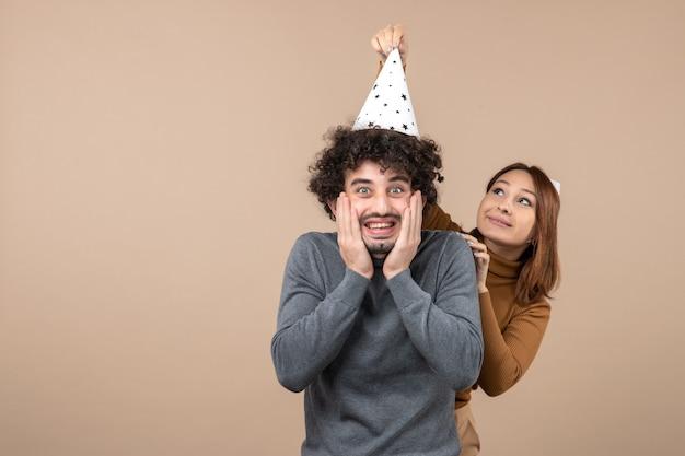 Le giovani coppie dolci emozionanti adorabili indossano la ragazza sorridente del cappello del nuovo anno che sta dietro il ragazzo su gray