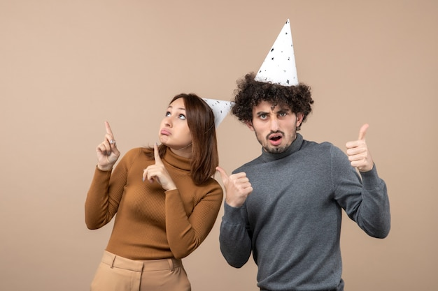 Lovely excited young couple wear new year hat girl looking above and standing near guy on gray image