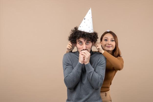 素敵な興奮した若いカップルは男の後ろに立って灰色で彼の耳を引っ張って新年の帽子の笑顔の女の子を着ています