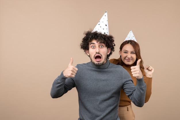 Le giovani coppie emozionanti adorabili indossano la ragazza sorridente del cappello del nuovo anno che sta dietro il ragazzo che fa il gesto perfetto su gray