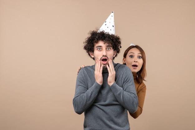 Le giovani coppie emozionanti adorabili indossano la ragazza sorridente del cappello del nuovo anno che sta dietro il ragazzo sorpreso su gray