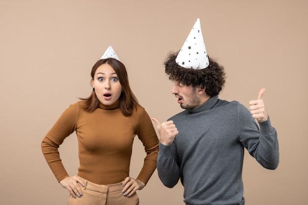 Le giovani coppie emozionanti adorabili indossano la ragazza sorpresa del cappello del nuovo anno che sta vicino al ragazzo sull'immagine grigia