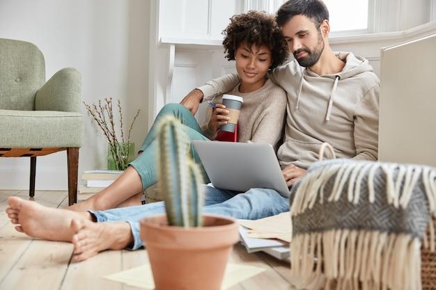 Прекрасная семейная пара обнимаются вместе, одеваются небрежно, наслаждаются домашней атмосферой, синхронизируют данные на портативном компьютере, работают над проектом семейного бизнеса, пьют горячий напиток, кактус на переднем плане