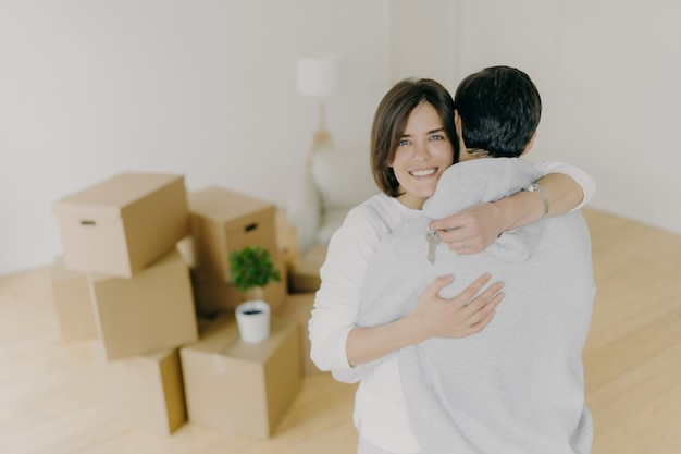 Lovely family couple embrace with love, hold keys from new apartment, move in own apartment