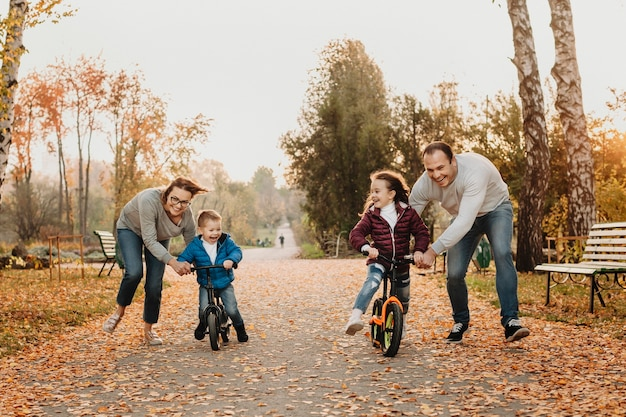 Lovely family playing with their kids while teaching them how to ride bicycles in the park.