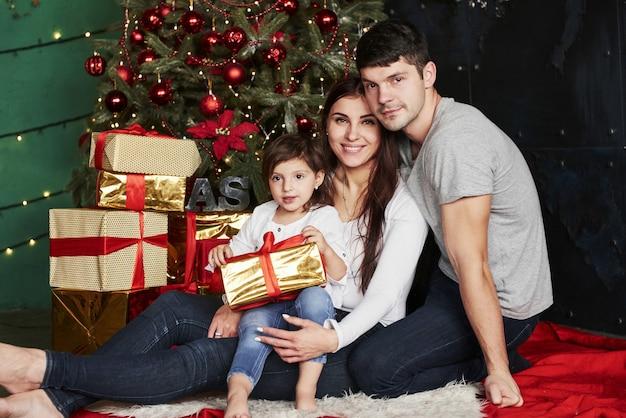 Прекрасная семья сидит возле елки с подарочными коробками зимним вечером, наслаждаясь проведением времени вместе.