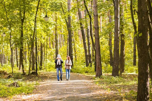 가을 숲에서 산책하는 사랑스러운 가족. 건강한 생활.