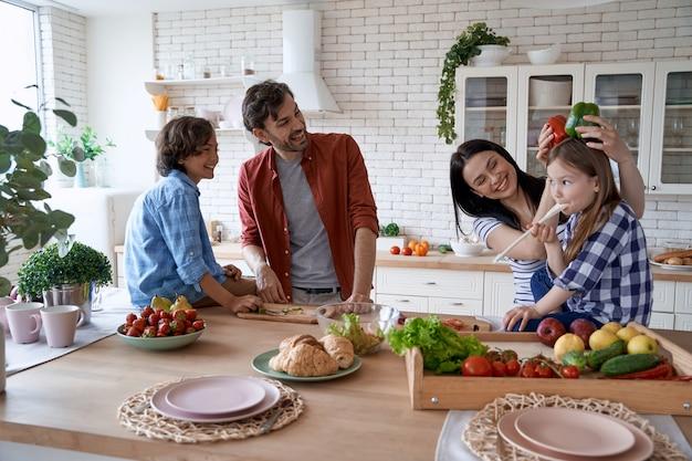 自宅のモダンなキッチンで一緒に料理をしながら楽しんでいる幸せな子供たちとの素敵な家族
