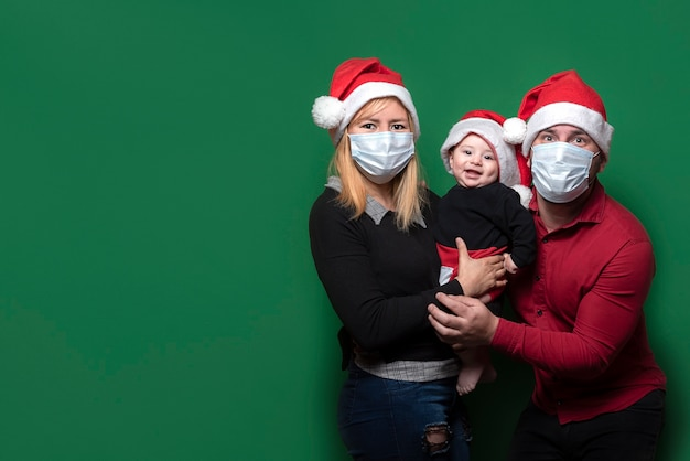 Lovely family with santa hat wearing mask
