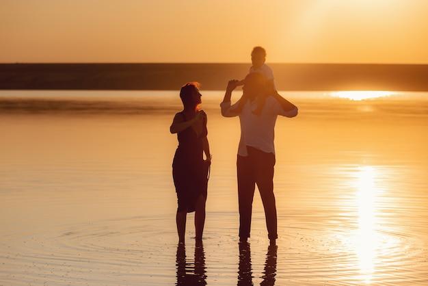 Милая семья с сыном на открытом воздухе на закате