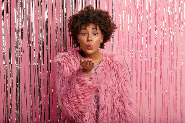 Lovely fashionable afro american woman in fur pink coat, makes hand gesture, sends air kiss, poses against rosy photo zone with tinsel, comes on party, flirts with handsome man, has minimal make up