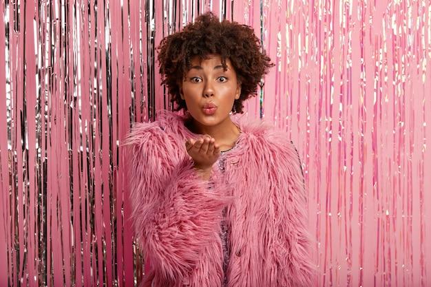 모피 핑크색 코트를 입은 사랑스러운 유행의 아프리카 계 미국인 여성, 손 제스처를 만들고, 공기 키스를 보내고, 반짝이는 장미 빛 포토 존에 대해 포즈를 취하고, 파티에오고, 잘 생긴 남자와 바람 피우며, 최소한의 메이크업을 가지고 있습니다.