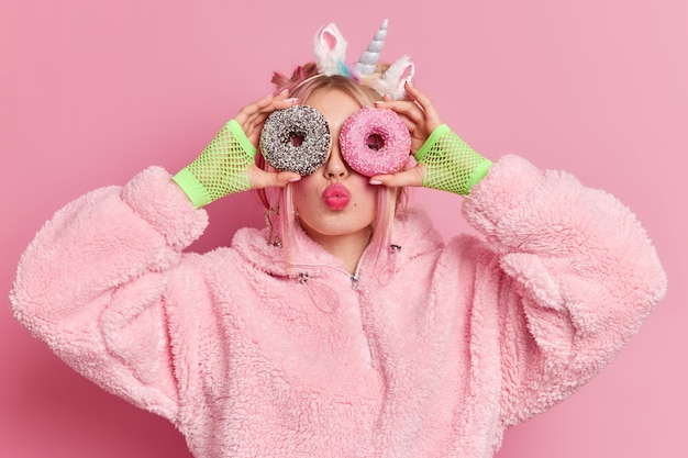 Lovely fashionable teenage girl holds glazed sweet doughnuts over eyes keeps lips rounded
