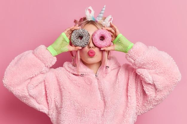 사랑스러운 유행 십대 소녀는 눈 위에 유약을 바른 달콤한 도넛을 들고 입술을 둥글게 유지합니다.