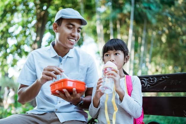素敵なお父さんが公園で娘に餌をやる