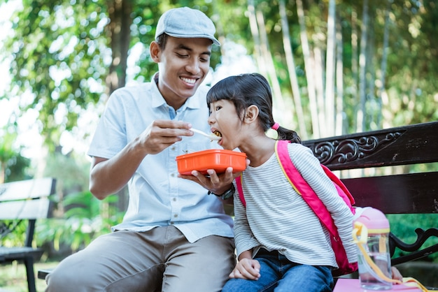 Lovely father feed his daughter in the park