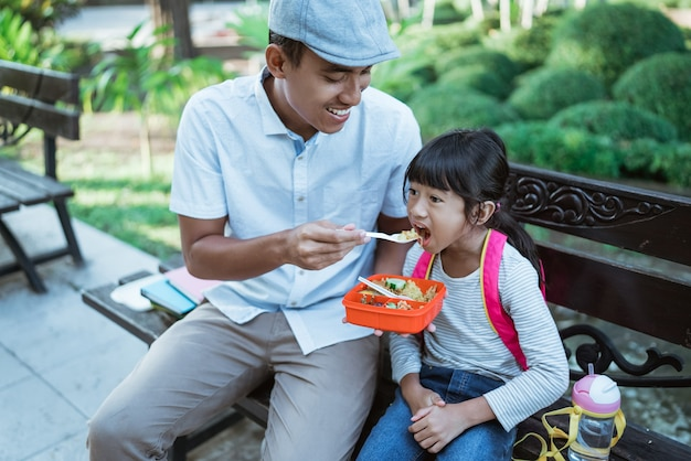 Lovely father feeds his daughter in the park