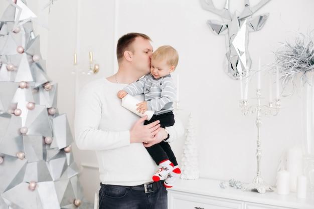 손에 작은 아들을 유지하고 그를 포옹하고 키스하는 사랑스러운 아버지