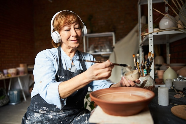 페인트 브러시로 점토 그릇을 그림과 도자기 스튜디오에서 음악을 듣고 사랑스러운 여성 세라믹 아티스트