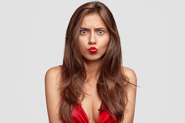 Lovely female has sullen expression, keeps lips round, wears red clothes and lipstick, looks angrily, poses against white wall. people, beauty, negative facial expressions concept