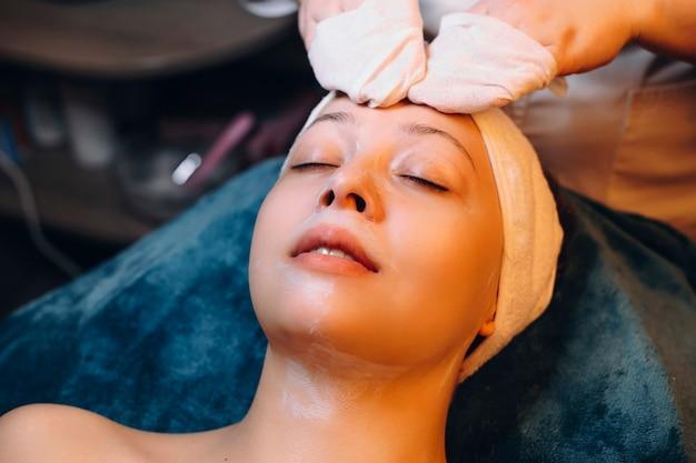 Прекрасная женщина, имеющая процедуру ухода за кожей в оздоровительном спа-курорте во время путешествия.
