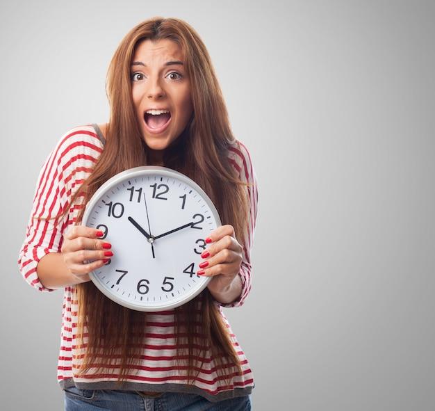 Прекрасный женщина держит круглые часы в руках.