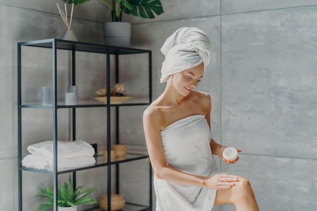 Lovely female model applies moisturising cream on leg, has healthy soft skin after taking bath