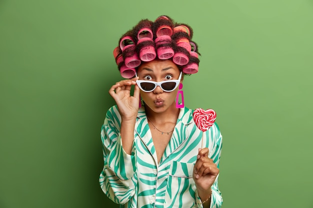 Lovely female model waits for kiss makes lips folded keeps hand on shades wears hair curlers stands stylish with heart shaped lollipop on stick isolated on green. fashionable woman in domestic clothes