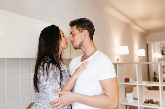 モダンなキッチンで白人男性と抱きしめる長い黒髪型の素敵な女性モデル