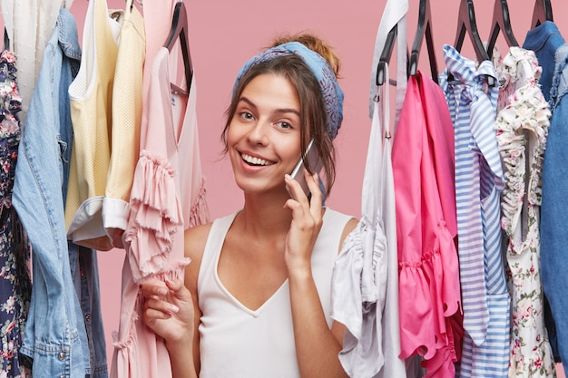 Lovely female wearing scarf on head and casual t-shirt, having good mood while speaking with someone over cell phone, standing near rack of clothes