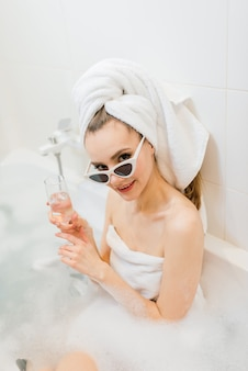 Lovely female with snow-white smile sits in the bathroom. stylish woman in towel on her head and sunglasses takes spa treatments at home or hotel
