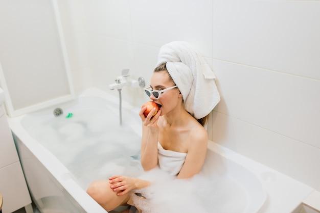 백설 공주 미소를 지닌 사랑스러운 여성이 화장실에 앉아 있습니다. 그녀의 머리와 선글라스에 수건을 입은 세련된 여성이 집이나 호텔에서 스파 트리트먼트를받습니다.