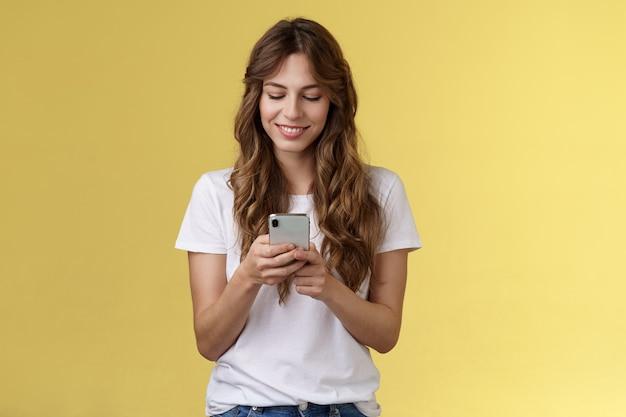 사랑스러운 여성스러운 부드러운 백인 소녀 흰색 티셔츠 청바지는 스마트폰 문자 메시지를 받고 웃는 여자 친구를 들고 기뻐하며 부드럽게 사랑스러운 미소 휴대 전화 화면 노란색 배경