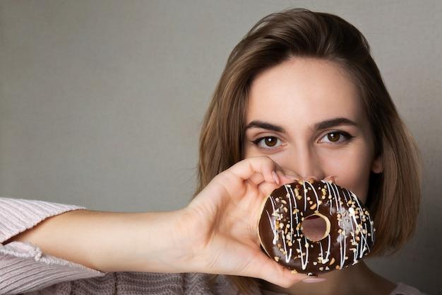灰色の背景にドーナツを保持しているナチュラルメイクの素敵な軽薄な女の子。テキスト用のスペース